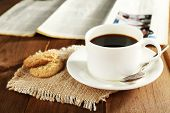 Cup of coffee with cookies on burlap cloth near newspaper on wooden table background