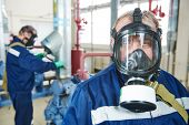 portrait of service engineer worker with gas mask at industrial compressor station for refrigeration or ammoniac chiller system at factory