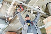 picture of engineering construction  - line electrician builder engineer worker at indoor construction site cabling - JPG