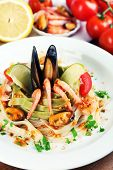 Tasty pasta with shrimps, mussels, tomatoes on plate on wooden background