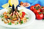 Tasty pasta with shrimps, mussels and tomatoes on plate on wooden background