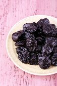 Plate with heap of prunes on color wooden background