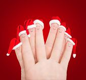 Fingers Faces In Santa Hats Against Red. Happy Friends Christmas Celebrating Concept