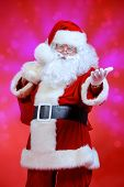 Portrait of happy Santa Claus with a big bag of gifts over festive red background.