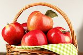 Wicker basket of red apples with green napkin on light background