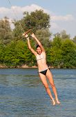 Cute teenage girl jumping into the river from the swinging rope on sunny summer day