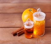 Bottles of essential oil and bath salt with orange and cinnamon on wooden background