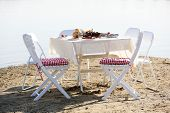 Table with dishware waiting for guests at beach