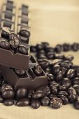 Coffee beans with chocolate glaze and dark chocolate on grey tablecloth