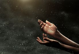 foto of nonverbal  - Extended female hands on dark stormy sky - JPG