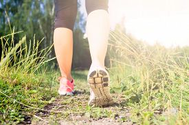 foto of crossed legs  - Walking or running exercise legs on green grass footpath in forest achievement fitness adventure and exercising in spring or summer nature - JPG