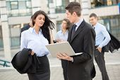 foto of team building  - Young businessman talking to his business partner in front of office building holding a laptop while in the background see the rest of the business team - JPG