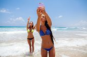 image of two women taking cell phone  - two happy sexy girls selfie smartphone on beach - JPG