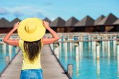 stock photo of jetties  - Beautiful woman on a wooden jetty at tropical resort - JPG