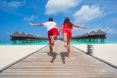 image of jetties  - Couple on a tropical beach jetty at Maldives - JPG
