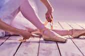 pic of ballet shoes  - Professional ballerina putting on her ballet shoes on the wooden floor on a pink background - JPG
