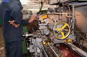 stock photo of factory-worker  - The worker turns a metal detail on the lathe