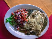 stock photo of enchiladas  - Mexican meal of chicken enchiladas with salsa verde and fresh tomato salsa - JPG