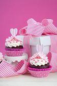 stock photo of cake stand  - Happy Mothers Day pink and white cupcakes on retro style cake stands and large gift box on vintage white wood table - JPG