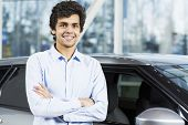 stock photo of beside  - Handsome young man standing besides car in showroom  - JPG