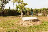stock photo of septic  - underground cement cylinder of lavatory cesspit in lawn yard - JPG
