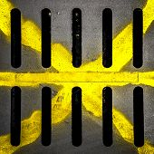 picture of spayed  - Detail of a manhole with yellow X drawn with paint spay - JPG