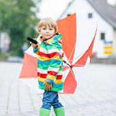 image of rainy day  - Little blond kid boy walking with big umbrella outdoors on rainy day - JPG