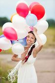 pic of latex woman  - Happy young woman holding in hands colorful latex balloons outdoors - JPG