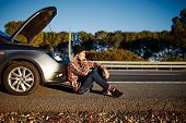 stock photo of cell  - Young brutal man sits near car talking on cell phone because his auto broken down - JPG