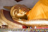 image of recliner  - blurry defocused image of golden reclining buddha statue in asian temple for background - JPG