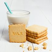 picture of milk  - Closeup of glass of milk and cookie with MILK sign against white wooden background - JPG