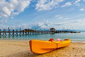 image of kayak  - Yellow kayak on beach and a pier against blue sky - JPG