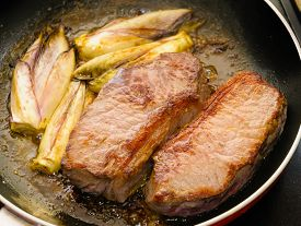 image of endive  - Cooked beef tenderloins with endives in a pan - JPG