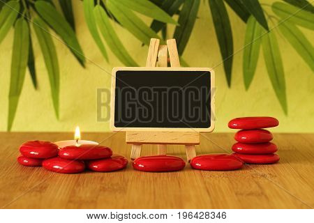 Small empty slate in width to write a message that is posed on an easel with red stones  columns on the ground in zen lifestyle with a candle all on wooden floor and green foliage background