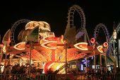 Passeios de imagem borrada / longa exposição de um parque de diversões brilhantemente iluminada