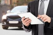 Insurance agent using tablet and car on background poster