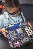 High angle view of concentrated elementary student examining circuit board on desk at electronics la poster