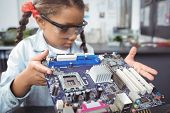 Concentrated elementary schoolgirl examining circuit board on desk at electronics lab poster