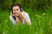 Augenzwinkernde Mädchen mit Kopfhörern auf dem Gras liegend