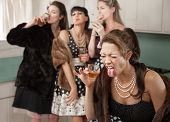 stock photo of foursome  - Woman reacts to strong alcohol while friends smoke and drink in the kitchen - JPG