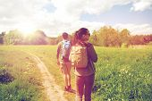 travel, hiking, backpacking, tourism and people concept - happy couple with backpacks walking along  poster