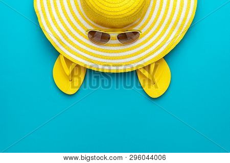 poster of Top View Of Yellow Sunglasses, Striped Summer Retro Hat And Flip-flops. Summer Concept On The Turquo