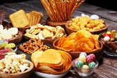 Salty Snacks. Pretzels, Chips, Crackers In Wooden Bowls On Table poster