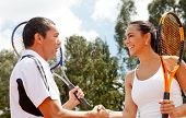 foto of young adult  - Couple handshaking at the tennis court after a match - JPG