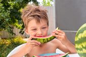 Beautiful Kid Eating Watermelon Outside In The Garden. Red Ripe Watermelon Eaten By The Boy. Healthy poster