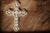 Artistic macro image of ornate stone cross on wood background with layers of texture added for effec
