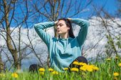 Girl In Hoodie Sitting On Green Meadow Among Flowers And Meditating In Nature Background. Woman Prac poster