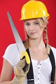 Woman with a hardhat and handsaw