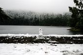 Miniature Snowman on a Stone Wall at Lake's Edge