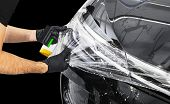 Car Wrapping Specialist Putting Vinyl Foil Or Film On Car. Protective Film On The Car. Applying A Pr poster